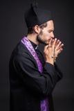 Junger katholischer betender Priester lizenzfreie stockbilder