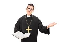 Junger katholischer Priester, der eine Bibel hält Lizenzfreie Stockfotos