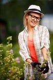 Junger kaukasischer blonder Damengärtner, der im Garten arbeitet Stockfotografie
