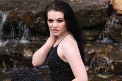 Junger kaukasischer Brunette berührt Hand zu ihrem Ohr Lizenzfreie Stockbilder