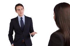 Junger kaukasischer Geschäftsmann, der eine Geschäftsfrau rügt Stockbild