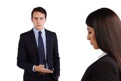 Junger kaukasischer Geschäftsmann, der Geschäftsfrau rügt Stockbild