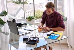 Junger kaukasischer Geschäftsmann, der an seinem Schreibtisch arbeitet Stockfoto