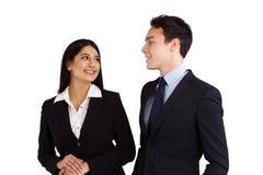 Junger kaukasischer Geschäftsmann lächelt an einer Geschäftsfrau Lizenzfreies Stockbild