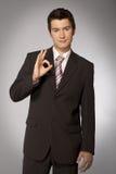 Junger kaukasischer Geschäftsmann, der okaygeste zeigt Stockbilder