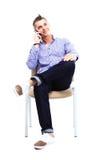 Junger kaukasischer gutaussehender Mann, der auf dem Stuhl lokalisiert sitzt Lizenzfreie Stockbilder