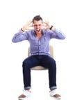 Junger kaukasischer gutaussehender Mann, der auf dem Stuhl lokalisiert sitzt Stockfotografie