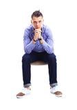 Junger kaukasischer gutaussehender Mann, der auf dem Stuhl lokalisiert sitzt Stockfoto