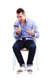 Junger kaukasischer gutaussehender Mann, der auf dem Stuhl lokalisiert sitzt Lizenzfreies Stockbild
