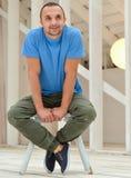 Junger kaukasischer gutaussehender Mann, der auf dem Stuhl sitzt Stockfotografie