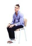Junger kaukasischer gutaussehender Mann, der auf dem Stuhl sitzt Stockfotos