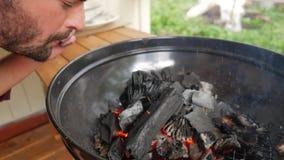 Junger kaukasischer Hippie, der Feuer im Grill beginnt Schwarze hölzerne Holzkohle, die im Bbq brennt HD slowmotion stock video