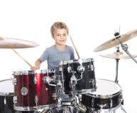Junger kaukasischer Junge spielt Trommeln im Studio gegen weißes backgrou Stockfotos
