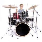 Junger kaukasischer Junge spielt Trommeln im Studio gegen weißes backgrou Stockfotografie