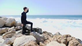 Junger kaukasischer lächelnder Mann, der den Ozean mit den Händen betrachtet, um voranzugehen und den Finger auf den Horizont bei stock video footage