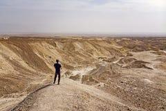 Junger kaukasischer Mann in der Baseballmütze, die allein in der Wüste bleibt und voran zum Horizont schaut Junge Reisendentdecku lizenzfreie stockfotos