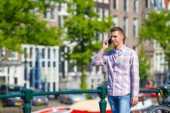 Junger kaukasischer Mann, der an durch Handy spricht Lizenzfreies Stockfoto