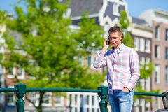 Junger kaukasischer Mann, der an durch Handy spricht Lizenzfreie Stockbilder