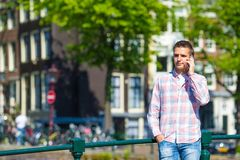 Junger kaukasischer Mann, der an durch Handy spricht Stockfotos