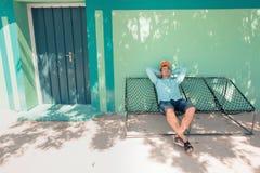 Junger kaukasischer Mann, der in einer angenehmen Trägheit der Hängematte des Wochenendenmorgens schwingt Stockfotos