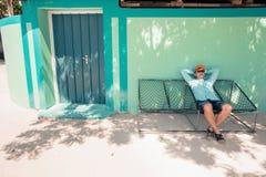 Junger kaukasischer Mann, der in einer angenehmen Trägheit der Hängematte des Wochenendenmorgens schwingt Stockfotografie