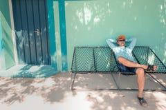 Junger kaukasischer Mann, der in einer angenehmen Trägheit der Hängematte des Wochenendenmorgens schwingt Stockfoto