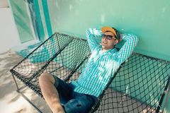 Junger kaukasischer Mann, der in einer angenehmen Trägheit der Hängematte des Wochenendenmorgens schwingt Stockbild