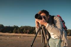 Junger kaukasischer Mann, der Foto von der Landschaft auf Küste macht Stockfotos