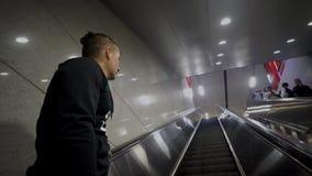 Junger kaukasischer Mann, der oben auf eine Rolltreppe am Flughafen, U-Bahn umzieht stock footage