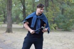 Junger kaukasischer Mann mit dem dunklen Haar hält die Taschenlampe in verlassenem Park mit sehr ernstem Gesichtsausdruck Dunkles stockfotografie