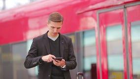 Junger kaukasischer Mann mit smarphone und Gepäck an der Station stock video