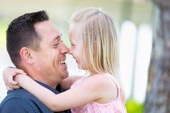 Junger kaukasischer Vater und Tochter, die Spaß am Park hat Stockbilder
