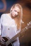 Junger kaukasischer weiblicher Musik-Spieler, der mit Gitarre gegen Schwarzes aufwirft Kombination des Blitzes und des Halogens b Stockbilder