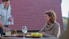 Junger Kellner gießt das Getränk herein zu den Gläsern auf dem Tisch stock video footage