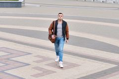 Junger Kerl allein in der Lederjacke, die hinunter die Straße auf Steinstraße geht stockfotos