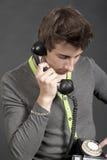 Junger Kerl, der am alten Telefon spricht stockfotos