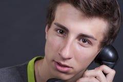 Junger Kerl, der am alten Telefon spricht lizenzfreie stockbilder