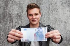 Junger Kerl, der Anmerkung des Euros 20 hält Stockbild