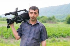 Junger Kerl, der auf der Natur mit einer Kamera stillsteht Lizenzfreies Stockbild