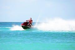 Junger Kerl, der auf einem Jet-Ski auf dem karibischen Meer kreuzt Stockfotografie