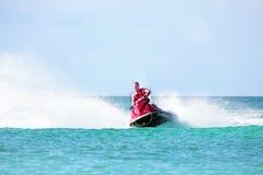 Junger Kerl, der auf einem Jet-Ski auf dem karibischen Meer kreuzt Lizenzfreie Stockfotos
