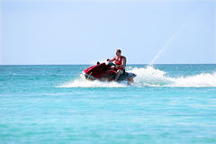 Junger Kerl, der auf einem Jet-Ski auf dem karibischen Meer kreuzt Lizenzfreie Stockbilder