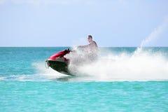 Junger Kerl, der auf einem Jet-Ski auf dem karibischen Meer kreuzt Stockbild