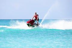 Junger Kerl, der auf einem Jet-Ski auf dem karibischen Meer kreuzt Stockfoto