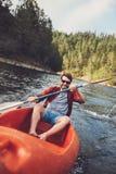 Junger Kerl, der auf einem See canoeing ist Stockfotografie