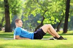 Junger Kerl, der auf einer Matte in einem Park liegt Stockbild