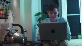 Junger Kerl, der den Computer sitzt an der Küche während Kessel kocht auf Ofen verwendet stock video