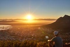 Junger Kerl, der den Sonnenaufgang über der Stadt aufpasst lizenzfreies stockbild
