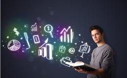 Junger Kerl, der ein Buch mit Geschäftsikonen liest Stockfoto