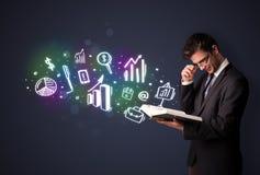 Junger Kerl, der ein Buch mit Geschäftsikonen liest Lizenzfreie Stockbilder